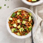Close up of a bowl of summer vegetable chili, served with avocado.