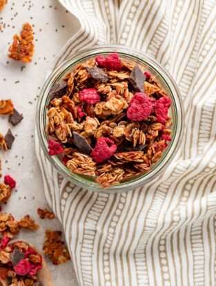 A small jar filled with raspberry chocolate chunk granola.