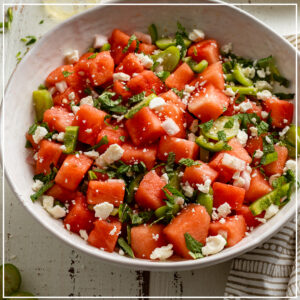 A large serving bowl of fresh watermelon salad with tomatillos, jalapenos, and lime dressing.