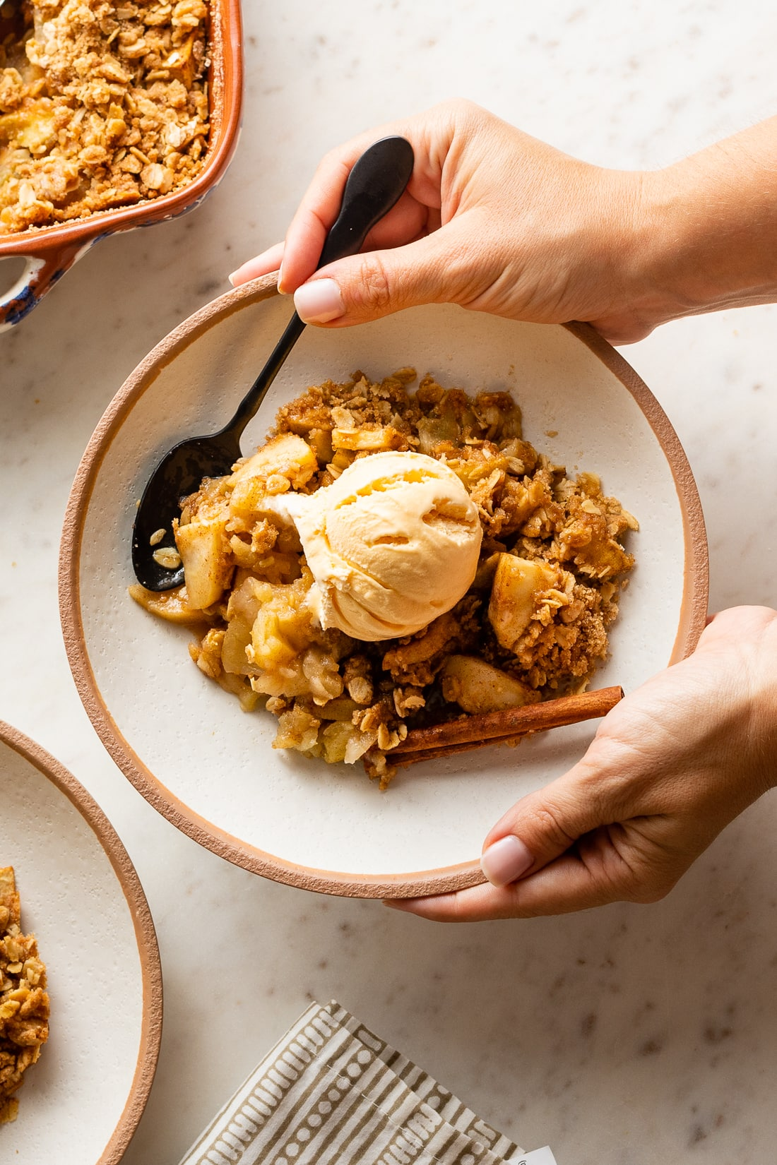 Hands holding a bowl of apple crisp with ice cream, caramel, and a spoon ready to eat!