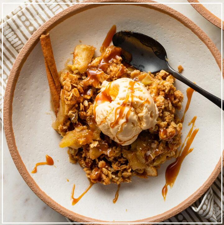 Old fashioned apple crisp in a bowl topped with vanilla ice cream and caramel sauce.