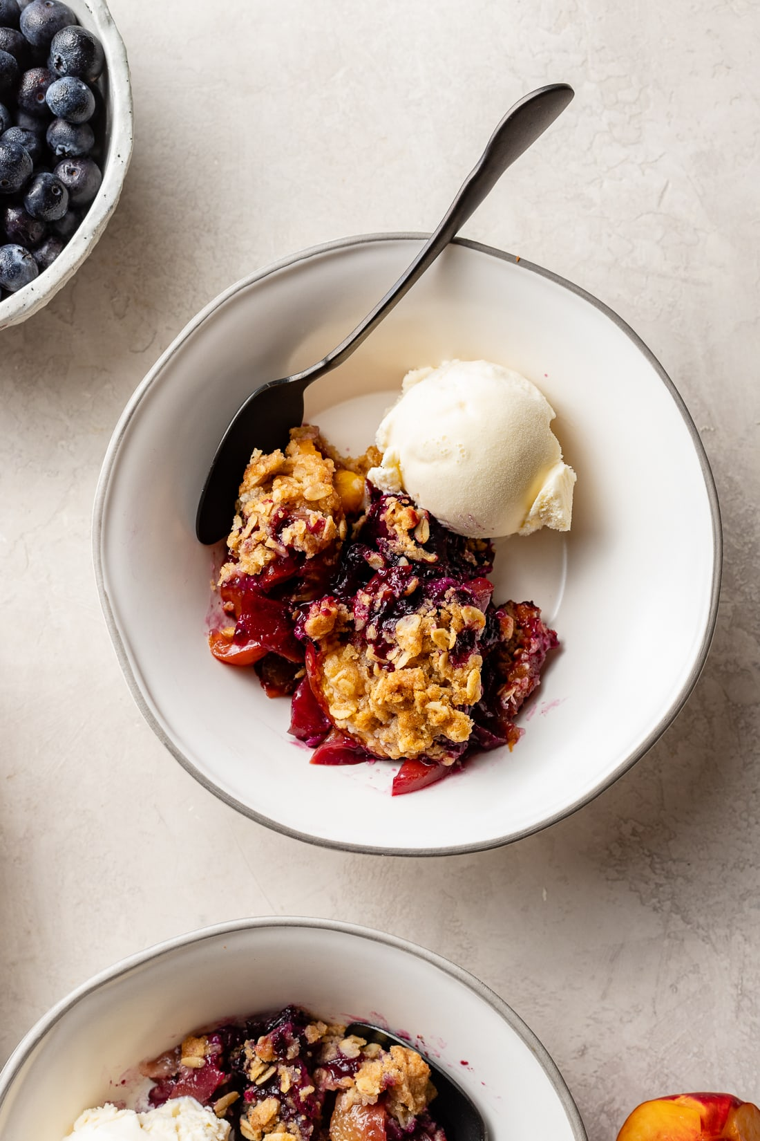 A serving bowl filled with blueberry nectarine crisp and a scoop of vanilla ice cream.