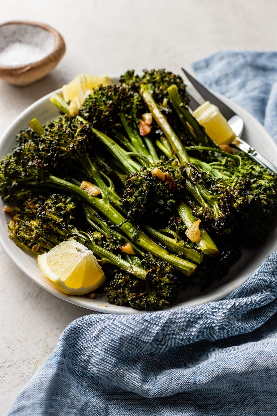Close-up image of roasted broccolini tips, slightly charred.