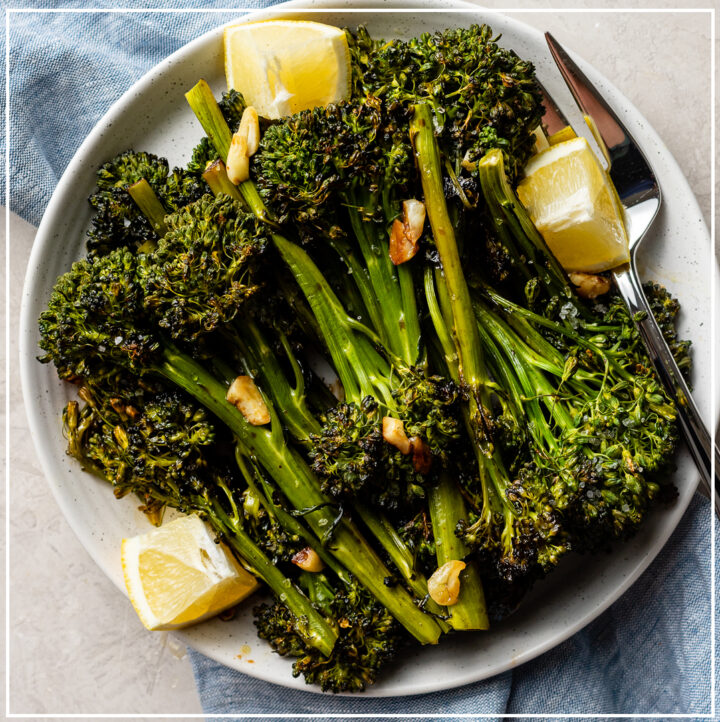 A plate of oven-roasted broccolini with soy sauce, garlic, salt, and lemon wedges.