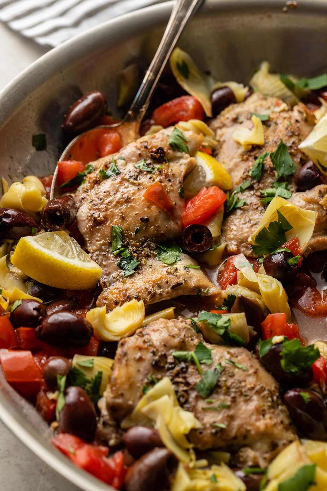 Close-up of seasoned Greek chicken cooked in a skillet.