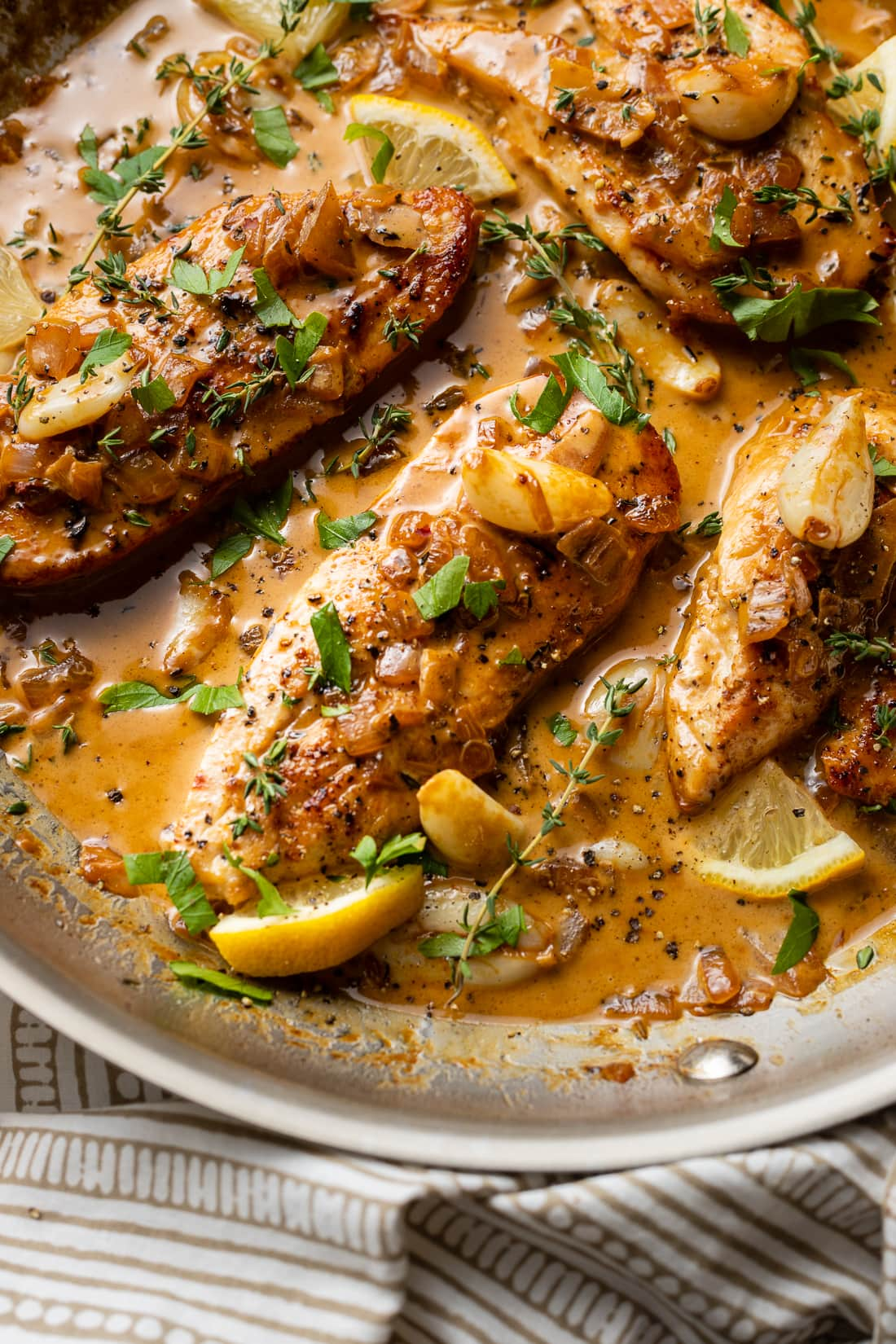 Close-up of creamy garlic chicken with herbs and lemon.