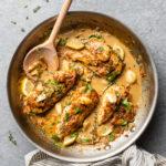 Creamy garlic chicken in a skillet with fresh herbs.