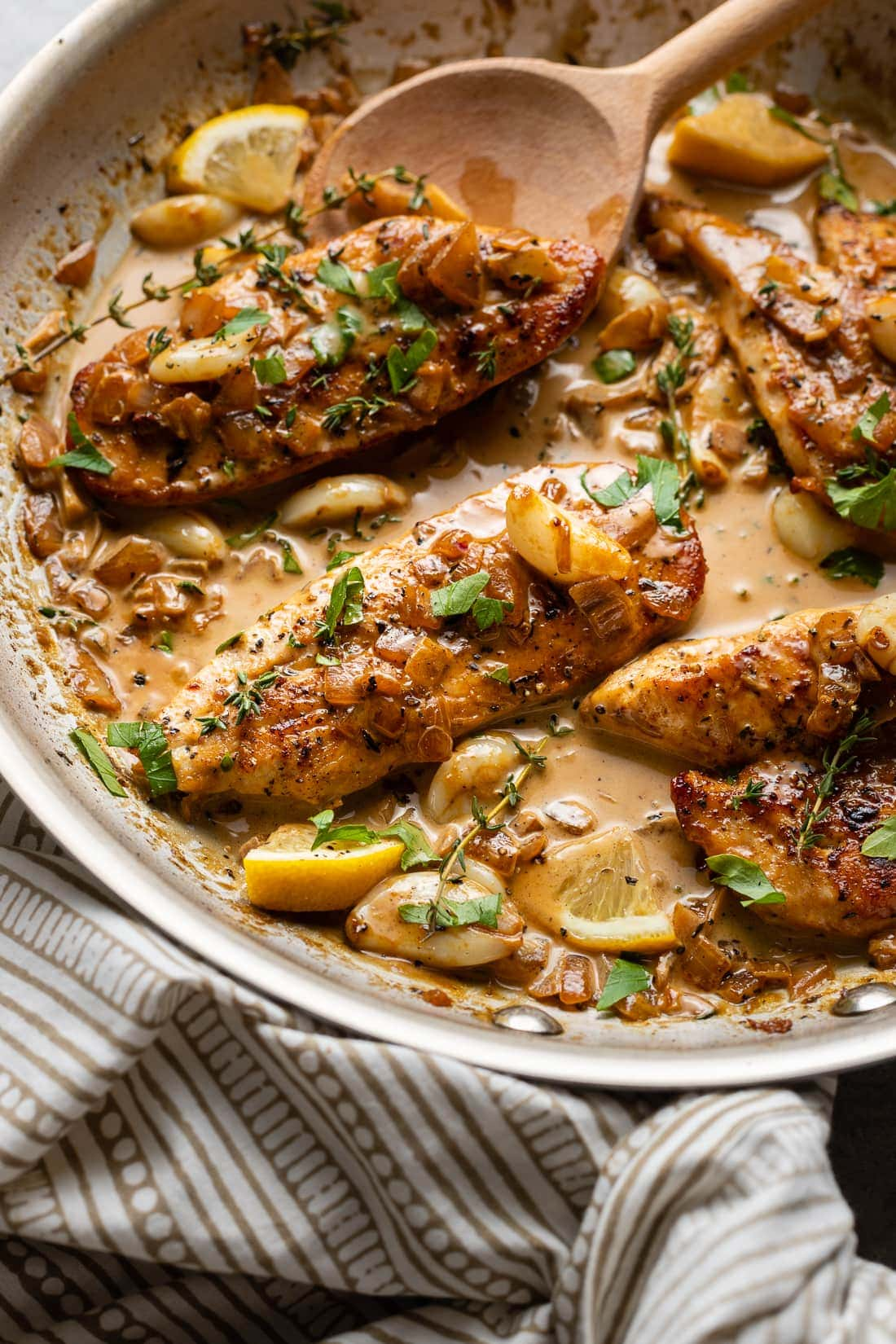 A spoon pouring sauce over creamy garlic chicken.