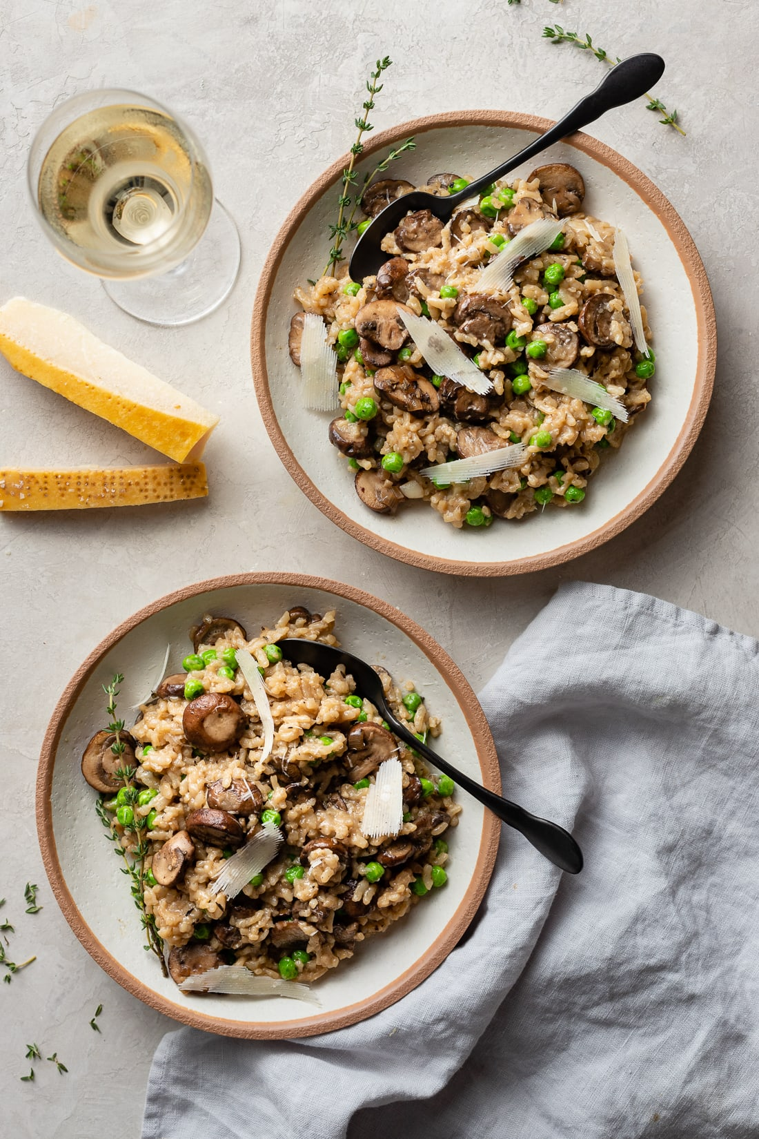 Two bowls of Instant Pot mushroom risotto, a glass of white wine, and Parmesan rinds on the table.