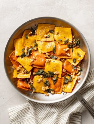 Skillet filled with pumpkin ravioli, sage brown butter sauce, crisped sage leaves, and walnuts.