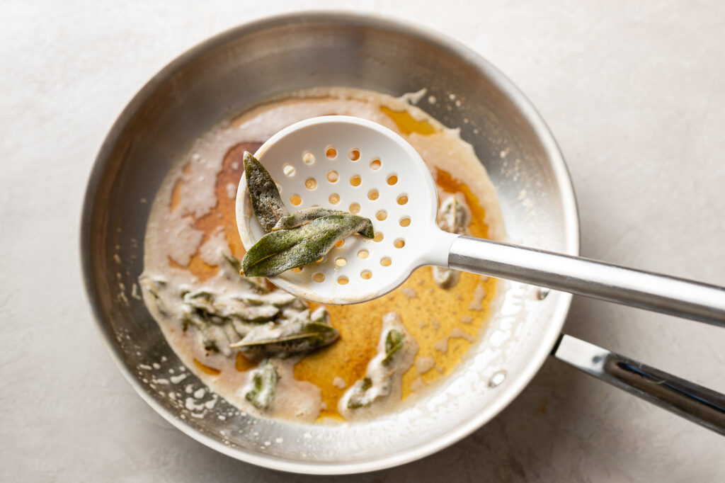 A white slotted spoon lifting crisped sage leaves out of the skillet.