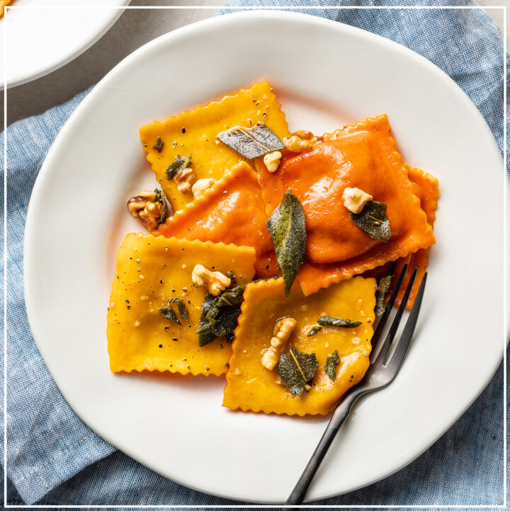 A plate with orange and yellow pumpkin ravioli garnished with sage brown butter sauce and toasted walnuts.
