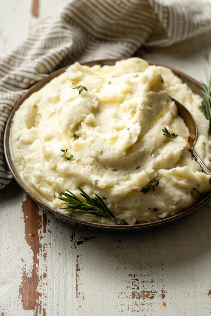 A bowl of fluffy garlic and herb mashed potatoes garnished with fresh rosemary and melted butter.