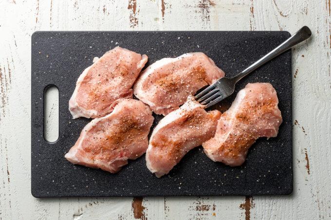 Seasoned pork chops on a plastic cutting board.