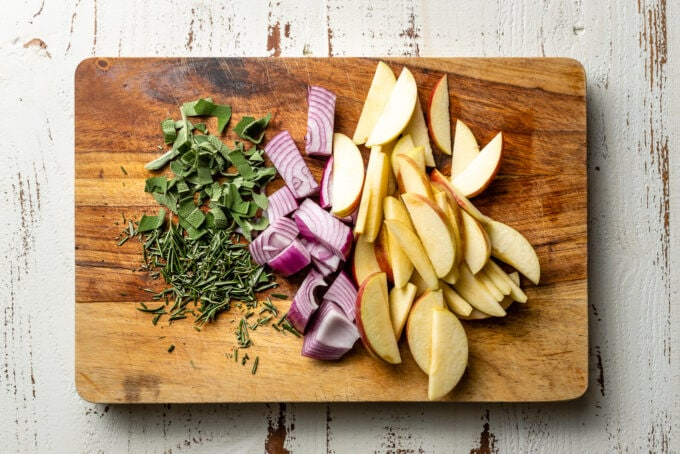 Chopped fresh rosemary and sage, chopped red onion, and chopped apples on a cutting board.