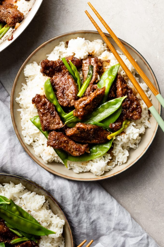 Bowls of Mongolian beef with snow peas served over white rice.