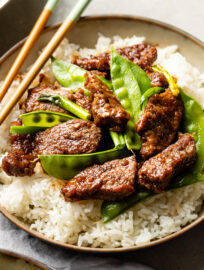 Close up of Mongolian beef with snow peas served over white rice.