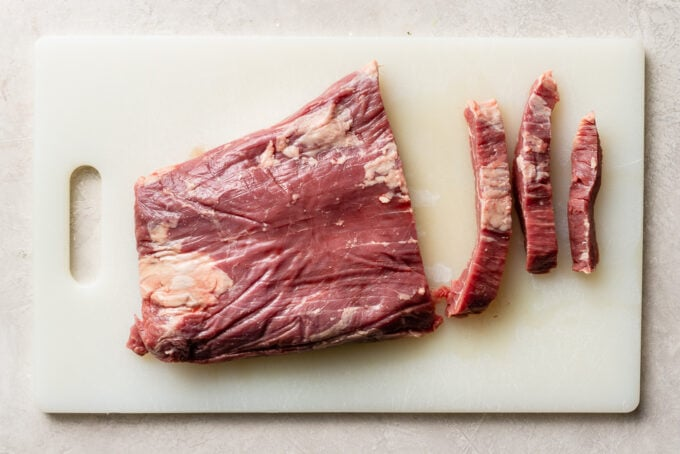 Flank steak on a cutting board, showing how to cut against the grain.