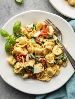 Plates of creamy Tuscan tortellini, ready to eat.