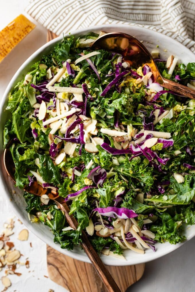 Healthy and easy kale Brussels sprout salad with red cabbage, sliced almonds, and lemon Parmesan dressing..