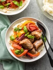 Bowls of Italian sausages, peppers, and onions served with creamy mashed potatoes.