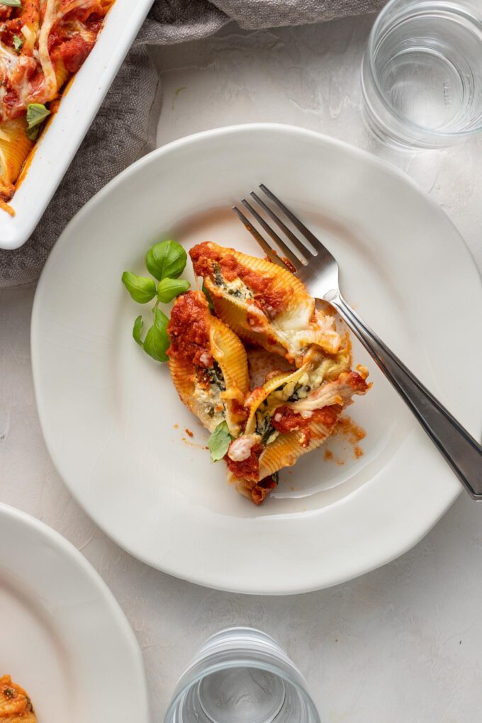 Small white plates with individual servings of spinach and ricotta stuffed shells.