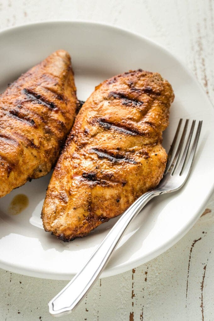 Juicy grilled chicken breasts on a white plate.