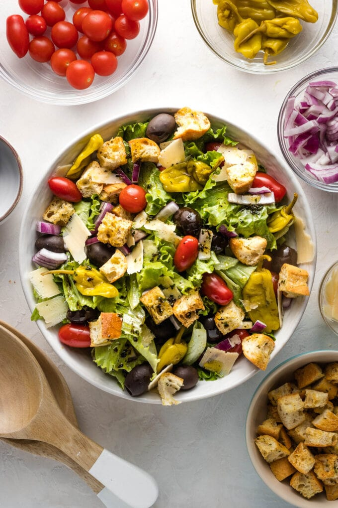 Bowl of salad surrounded by extra veggies and salad tongs ready to serve.