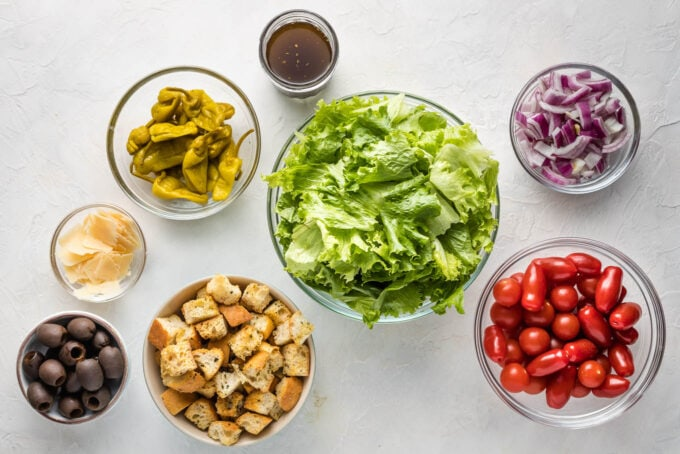 Prep bowls filled with washed romaine lettuce, Pepperoncini peppers, red onions, tomatoes, cheese, black olives, and croutons.
