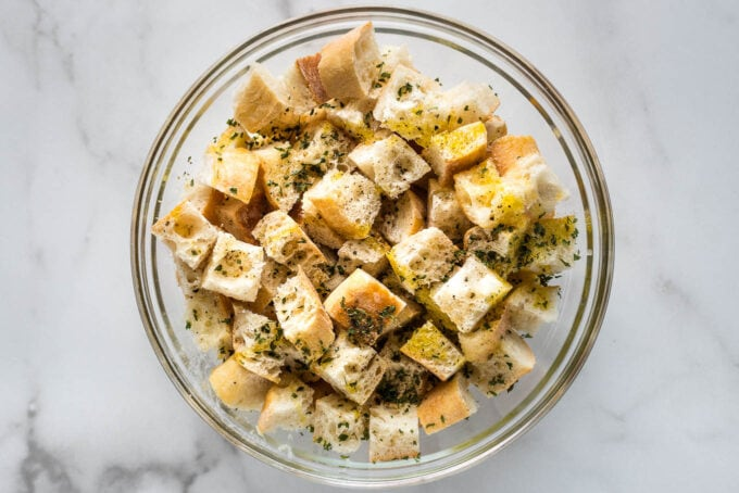 Olive oil, butter, and seasoning drizzled on bread cubes.
