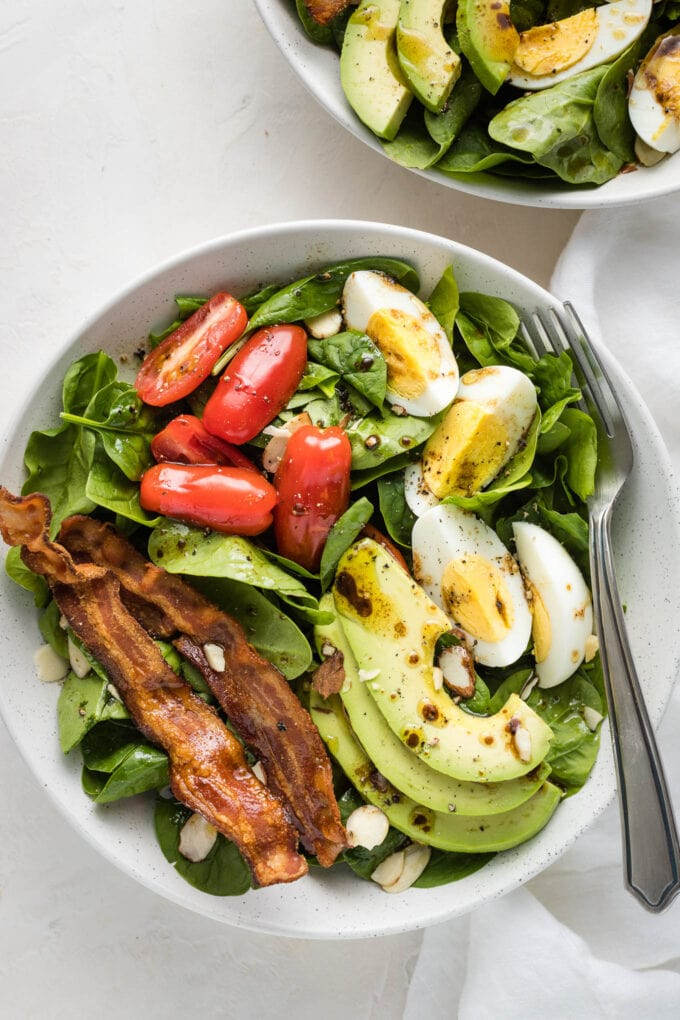 Spinach salad with bacon, hard-boiled eggs, avocado, tomatoes and a vinaigrette dressing.