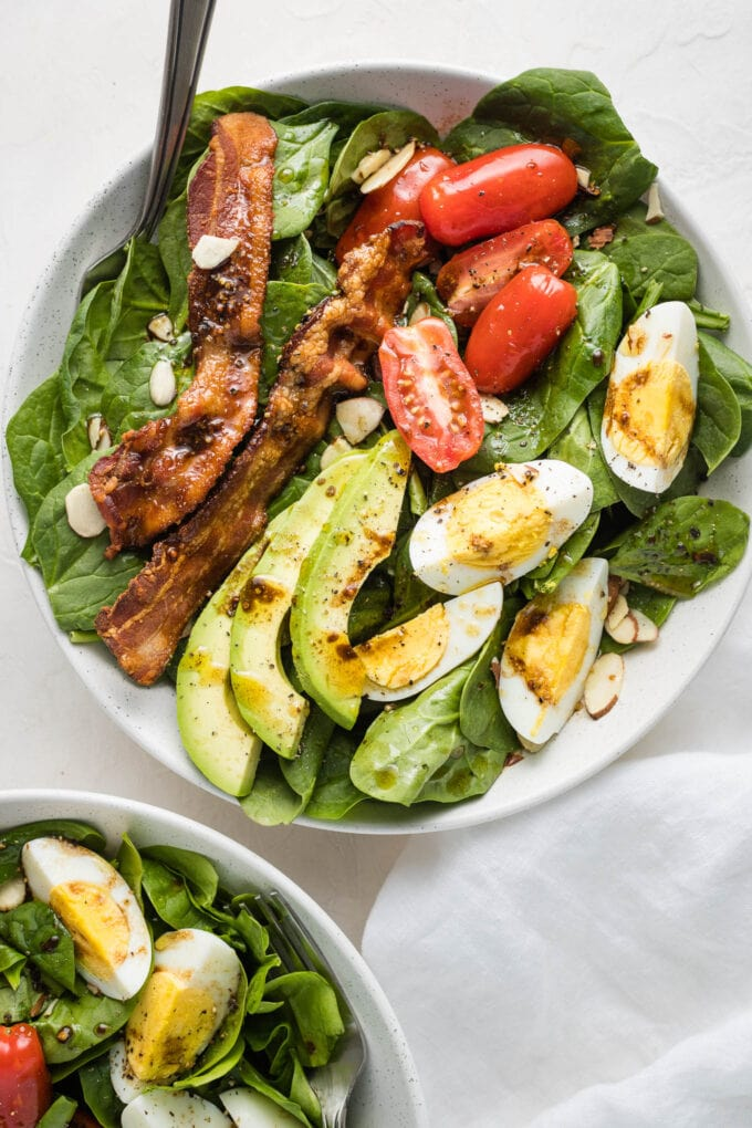 Spinach salad with bacon and eggs in a white bowl.