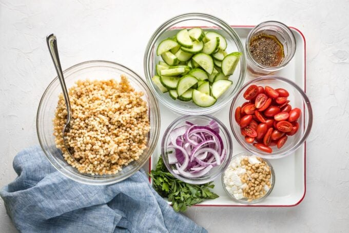 Pearl couscous, chopped cucumber, cherry tomatoes, red onion, feta, parsley, and salad dressing in small bowls.