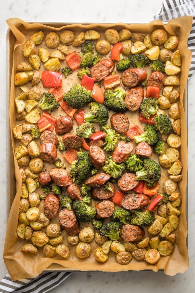 Large sheet pan holding roasted chicken sausage, broccoli, peppers, and baby potatoes.