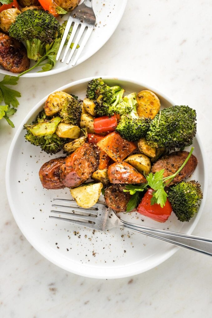 Small white plate with a serving of sausage, broccoli, pepper, and potatoes.