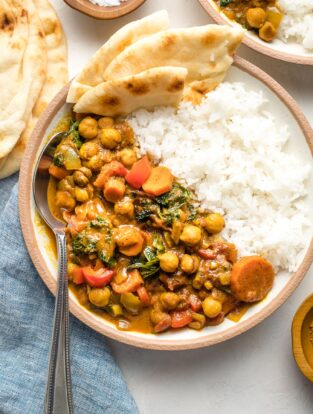 Bowl of Instant Pot chickpea curry served with rice and naan.