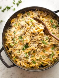 Large skillet full of sausage noodle casserole ready to serve.