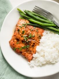 Plate with a salmon filet, rice, and green beans.
